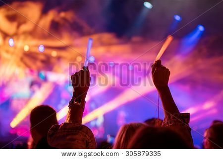 Young Teenager Girl Fan Raised Up Two Hands With Colored Glowing Sticks Supporting Favorite Popular