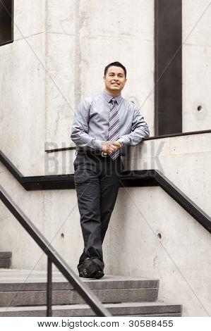 Empresario hispano - apoyándose en el carril de la escalera