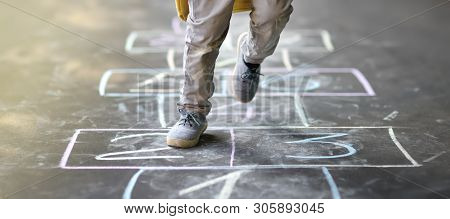 Closeup Of Little Boy's Legs And Hopscotch Drawn On Asphalt. Child Playing Hopscotch Game On Playgro