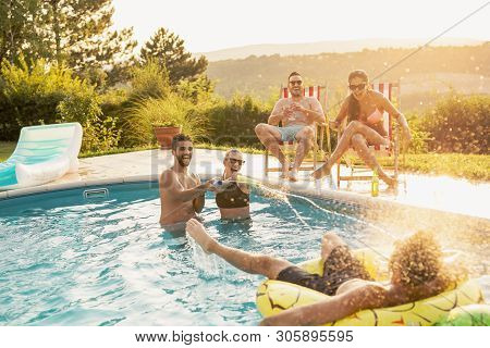 Group Of Friends At A Poolside Summer Party, Having Fun In The Swimming Pool, Drinking Beer And Spla
