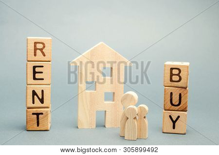 Wooden Blocks With The Word Rent Or Buy And A Family Stands Near The House. Make The Right Decision.