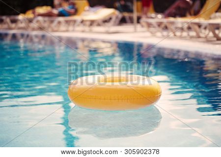 floating ring on blue water swimpool with waves reflecting in the summer sun