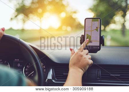 Close-up Of Woman Using Gps Navigation In Mobile Phone While Driving Car At Sunset