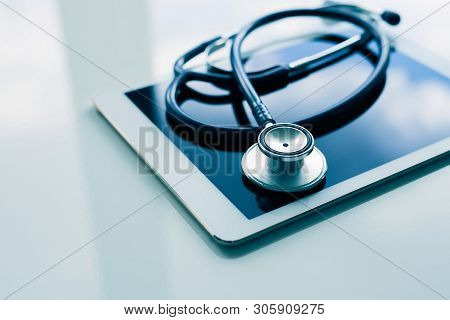 Medical Equipment On Table. Blue Stethoscope And Tablet On White Background.