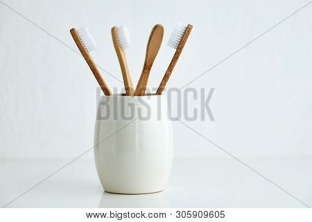 Four Bamboo Toothbrushes In A Glass
