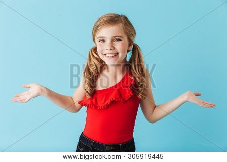 4323c8b3285a Cheerful little girl wearing swimsuit standing isolated over blue  background, having fun