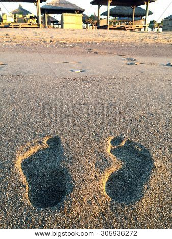 Footprints In The Sand At Sunset. Beautiful Sandy Tropical Beach With Sea Waves. Footsteps On The Sh