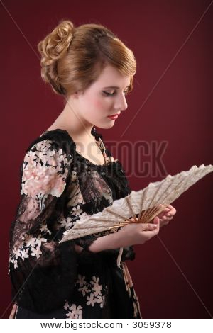 pretty young lady in old time ball dress with fan in style of the end of XIX century poster