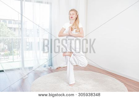 Yoga Time. Beautiful Woman Is Practicing Yoga At Home, Girl Doing Vrikshasana Agains Exercise, Stand