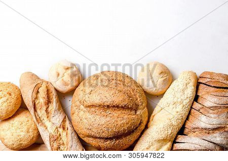 Assortment Of Different Types Of Bread, Loaf, Baguettes, Loaves, Rolls With Ears Of Wheat On White B