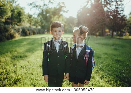 two schoolchildren looking at the room, boy with schoolbag, outdoor, at sunset poster