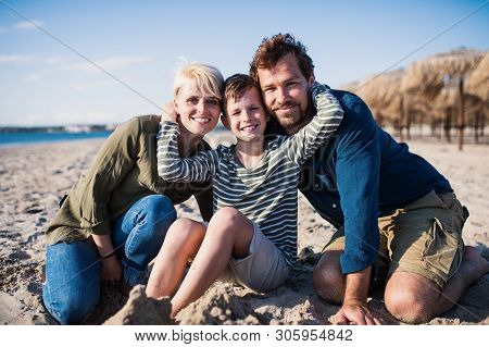 Young Family With Small Boy Sitting Outdoors On Beach, Looking At Camera.