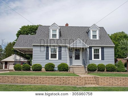 Little Blue Cape Cod House with Tan Brick Wall
