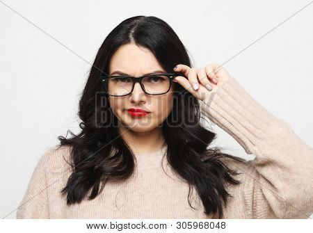 lifestyle, emotion and people concept - young woman wearing eyeglasses looks incredulously and reflects