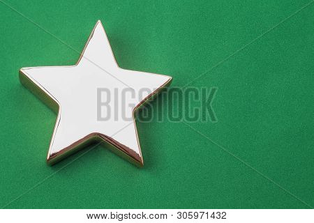 Image Shows An Golden X-mas Star, Isolated On Green Background With Space For Text