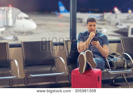 Middle Age Man Tourist Using Smart Phone In Airport Terminal Looking At Flight Schedules - Traveller