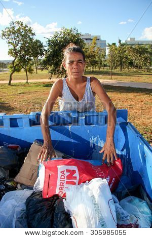 Brasilia, D.f., Brazil- June 11, 2019: A Poor Lady Digging Through The Trash In An Affluent Neighbor