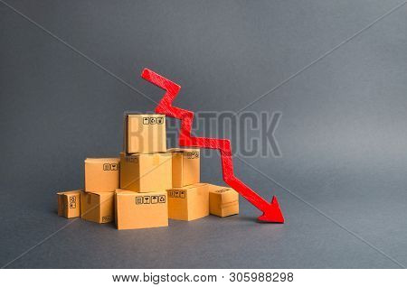 A Pile Of Cardboard Boxes And A Red Arrow Down. The Decline In The Production Of Goods And Products,