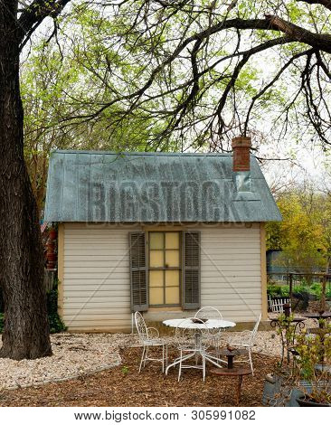 Small Cabin With A  Blue Tin Roof In Wooded Area With A Table In Mulched Area