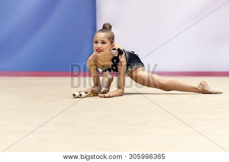 Little talented gymnast girl performs in a rhythmic gymnastics competition, dancing with clubs, active healthy childhood, beautiful sport for girls poster