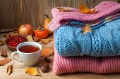 autumn clothes on a wooden background, sweaters, knitwear, wool. Leaves, bumps, acorns, berries, apple, pears, persimmons, tea on the table. poster