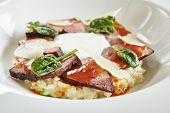 Exquisite Serving White Restaurant Plate of Risotto with Pecorino Cheese and Warm Roast Beef. Beautiful Delicacy Italian Veal Paella on Dark Stone and Leaves Background poster