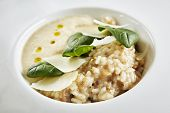 Beautiful Serving White Restaurant Plate of Risotto with Cep Mushroom Stew, Parmesan Cheese and Greens. Exquisite Delicacy Italian Boletus Paella on Dark Stone and Leaves Background poster