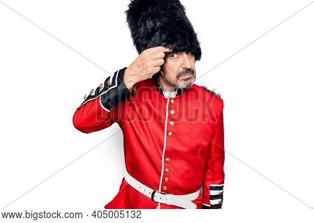 Middle age handsome wales guard man wearing traditional uniform over white background pointing unhappy to pimple on forehead, ugly infection of blackhead. Acne and skin problem