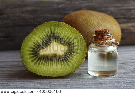 Kiwi Seed Oil In A Glass Jar With Fresh Halved Kiwifruit On Old Wooden Background.anti-aging Skin Ca