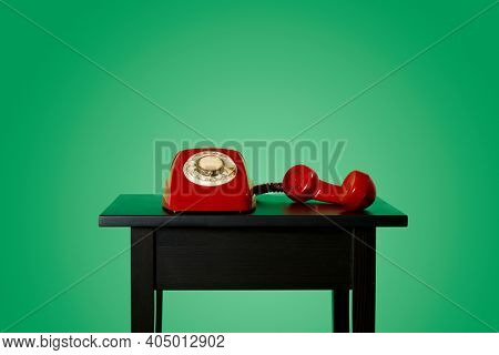 a red landline rotary dial telephone, with its handset off the hook on a black wooden table, on a green background