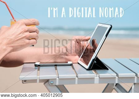 closeup of a young caucasian man on the beach, sitting at an outdoors table, using a digital tablet, while is having a refreshing orange beverage, and the text I am a digital nomad on top