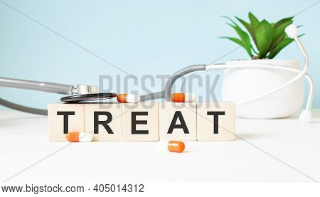 The Word Treat Is Written On Wooden Cubes Near A Stethoscope On A Wooden Background. Medical Concept