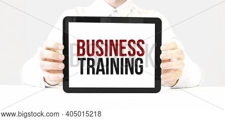 Text Business Training On Tablet Display In Businessman Hands On The White Bakcground. Business Conc