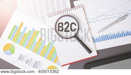 Magnifying Glass On B2C Text On Notepad, Dice, Spectacles, Pen, Laptop Calculator On Wooden Table -