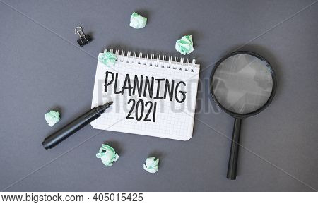 Paper Notepad With Text Planning 2021, Crumpled Papers Sheets And Magnifier Glass On Dark Background
