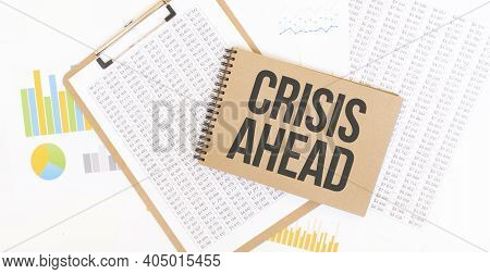 Text Crisis Ahead On Brown Paper Notepad On The Table With Diagram. Business Concept