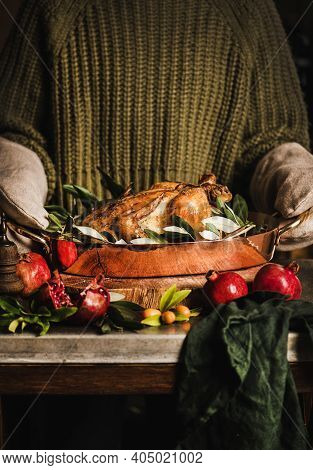 Woman In Knitted Sweater And Kitchen Mittens Holding Whole Roasted Chicken For Holiday Festive Dinne