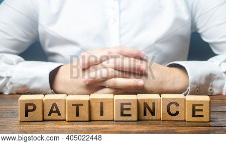 Man Folded His Hands On A Background Of Blocks With The Word Patience. Patience In Anticipation, Per