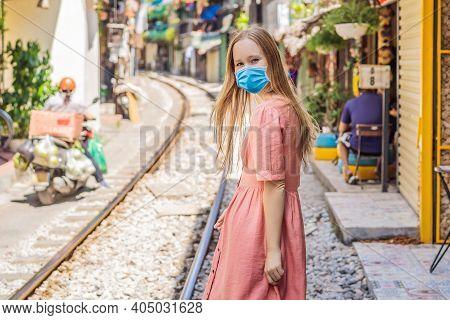 Woman Wearing A Medical Mask During Covid-19 Coronavirus Is Walking Of Hanoi City Railway. Perspecti