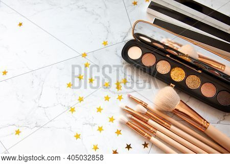 Flat Lay Composition Of Decorative Cosmetic Of Eyeshadow Palette And Different Size Of Makeup Brush.