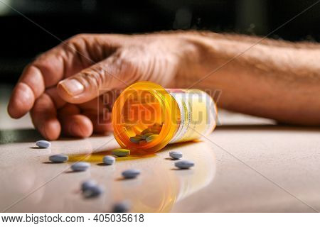 Prescription Medication Spilling On To The Floor With An Addicts Hand In Background. Depicting Curre