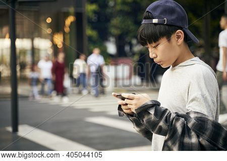 Teenage Asian Child Looking At Cellphone While Walking On Street