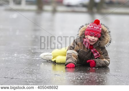 Funny Boy Fell Down While Skating. The Child Lies On The Ice In The Winter.