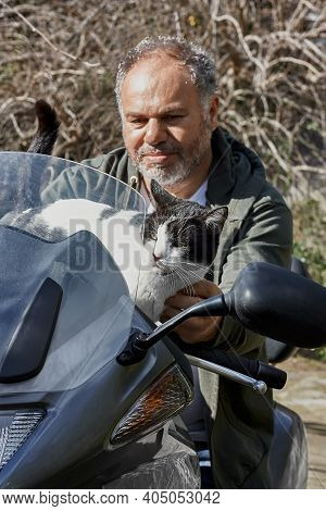 Bearded Mature Gray-haired Man With His Elderly Black And White Cat Ride A Motorcycle. Friendship, L