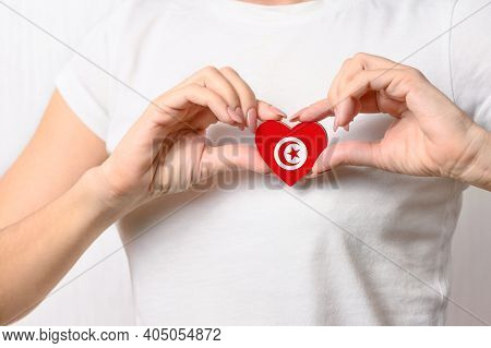 Love Tunisia. The Girl Holds A Heart In The Form Of The Flag Of Tunisia On Her Chest. Tunisian Conce