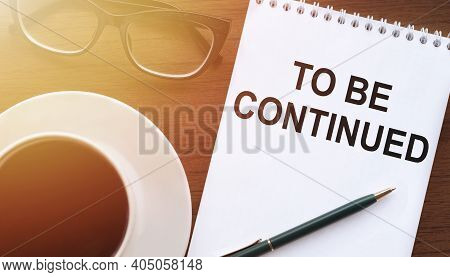 To Be Continued - Text On Paper With Cup Of Coffee And Glasses On Wooden Background In Sinlight.
