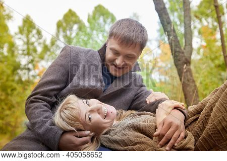 Middle-aged Couple Walking In The Park On An Autumn Day.
