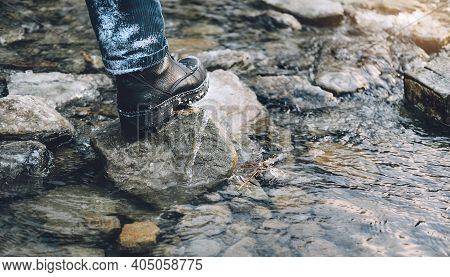 Hiking Shoes On Hiker Outdoors Walking Crossing Mountain Creek. Man On Hike Trekking In Nature. Clos