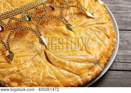 Traditional Galette Des Rois With Decorative Crown On Wooden Table, Closeup