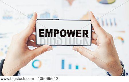Closeup On Businessman Holding A Smartphone With Text Empower.